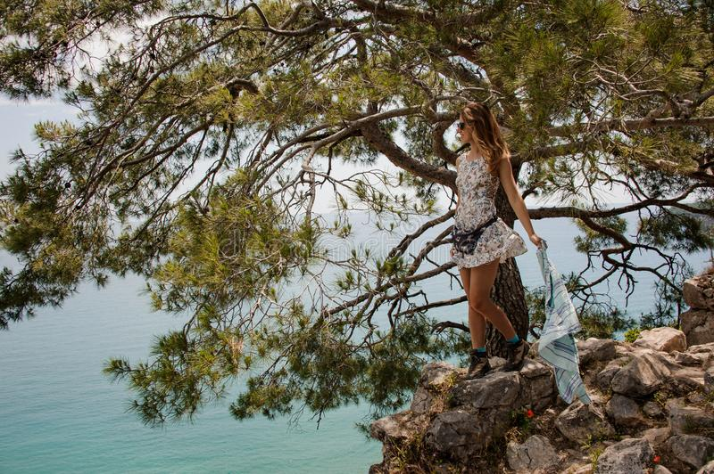 Girl in the light dress standing on the rock under the tree royalty free stock images