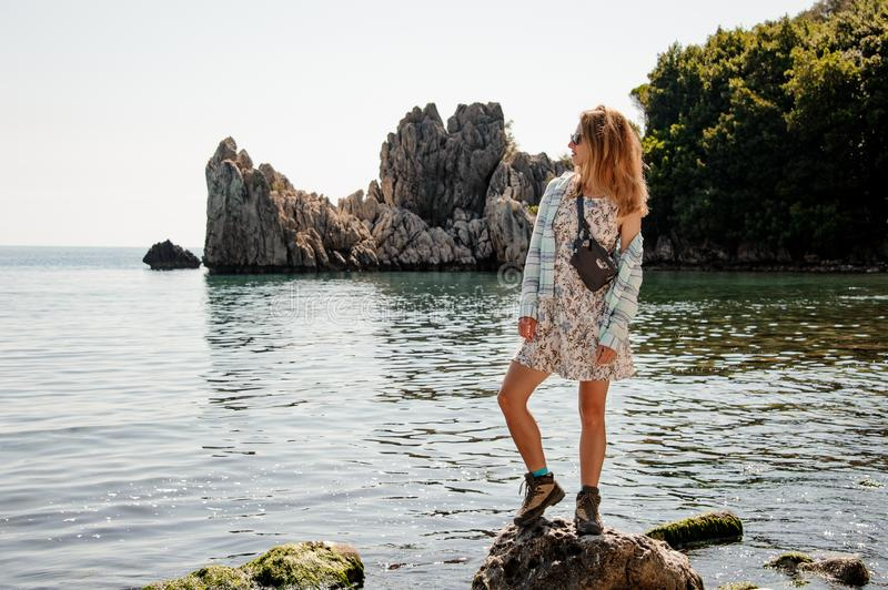 Girl in the light dress standing on the rock on the sea royalty free stock image