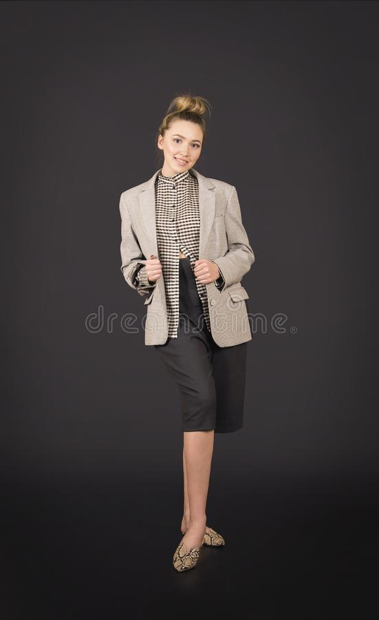 A girl in a light jacket and dark breeches posing. Studio shooting on a dark background stock photo