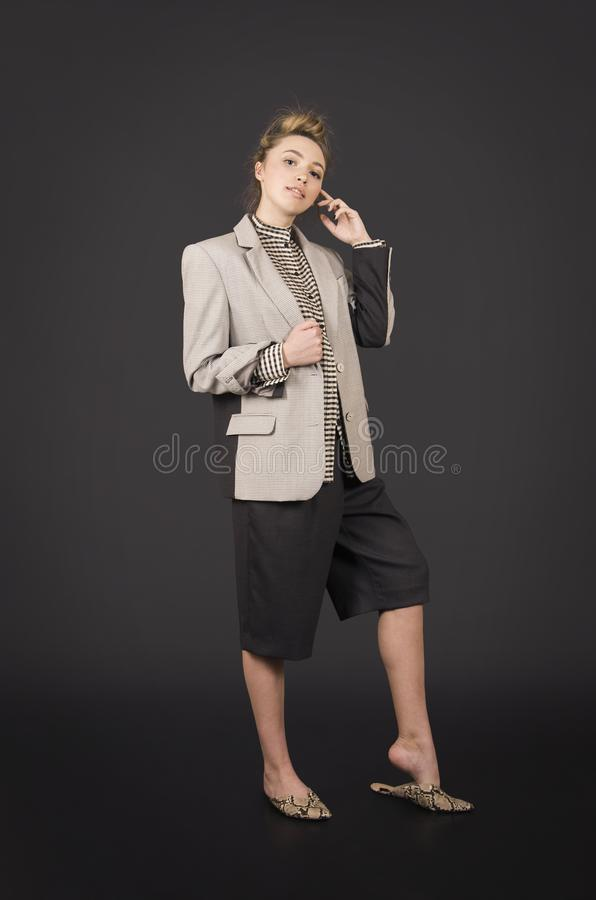 A girl in a light jacket and dark breeches posing. Studio shooting on a dark background royalty free stock images