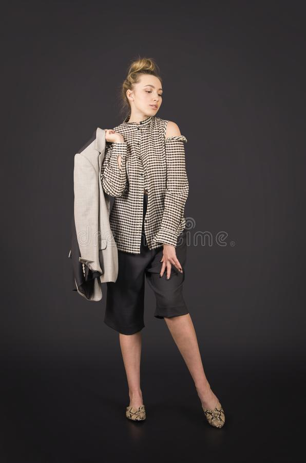A girl in a light jacket and dark breeches posing. Studio shooting on a dark background royalty free stock photo
