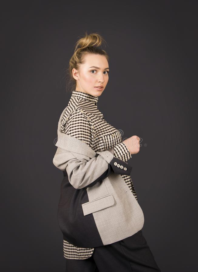 A girl in a light jacket and dark breeches posing. Studio shooting on a dark background royalty free stock photography