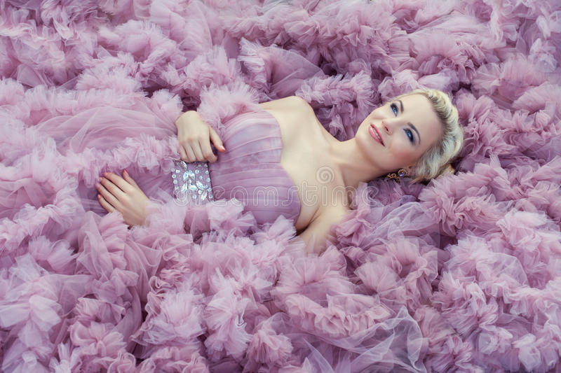 Girl in light pink dress. Beautiful young blond girl lying on a lush pink dress. Ball Gown gently pink color stock photography
