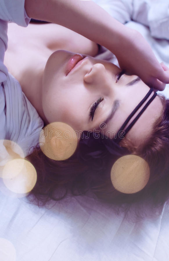 Beautiful young girl lying on the bed royalty free stock image