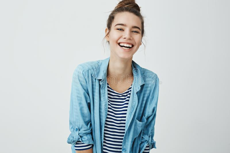 Girl likes funny jokes. Smart good-looking student with bun hairstyle trembling from laugh, smiling positively and being. In great mood while standing over gray stock photos
