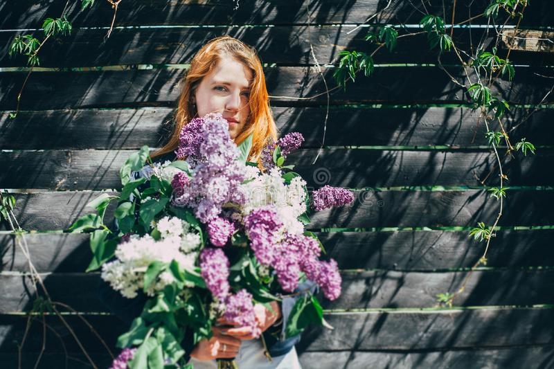 Girl with a lilac bouquet of lilac in the garden. girl tearing the lilac in the garden stock image