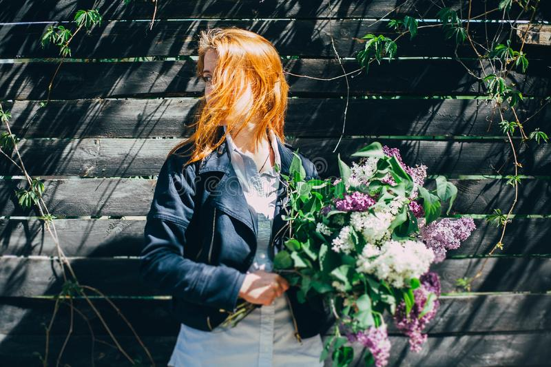 Girl with a lilac bouquet of lilac in the garden. girl tearing the lilac in the garden royalty free stock images