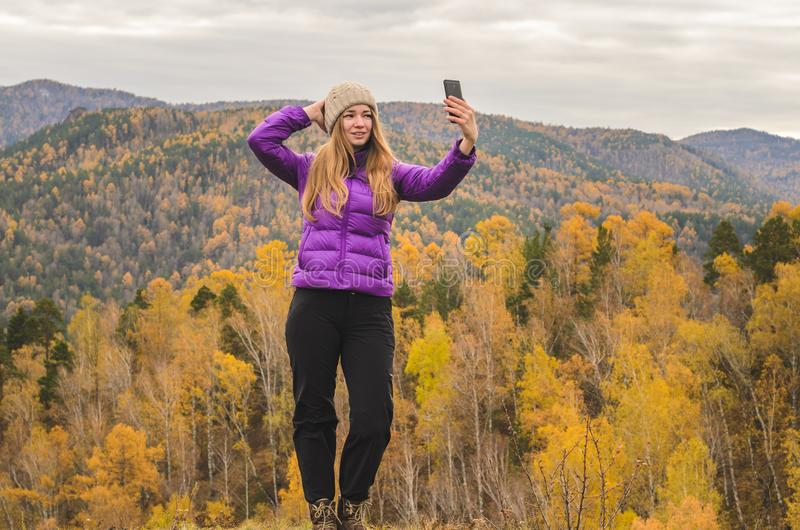 A girl in a lilac jacket makes a salfi on a mountain, a view of the mountains and an autumnal forest by a cloudy day royalty free stock images