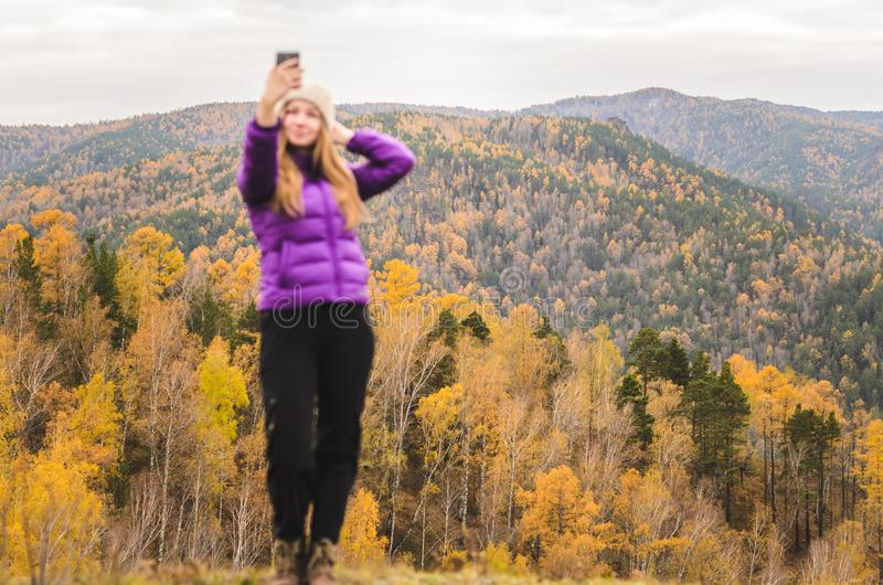 A girl in a lilac jacket makes a salfi on a mountain, a view of the mountains and an autumnal forest by a cloudy day. Free space for text royalty free stock photos