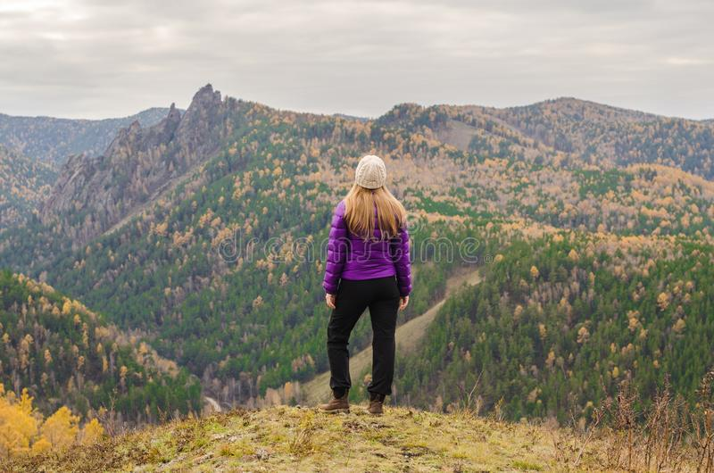 A girl in a lilac jacket standing on a mountain, a view of the mountains and an autumn forest royalty free stock images