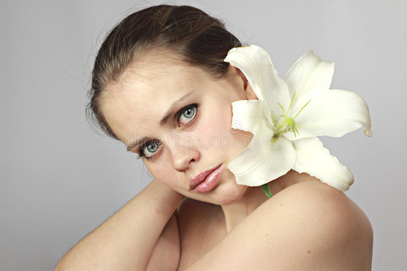 Girl with a lily on a shoulder stock photo