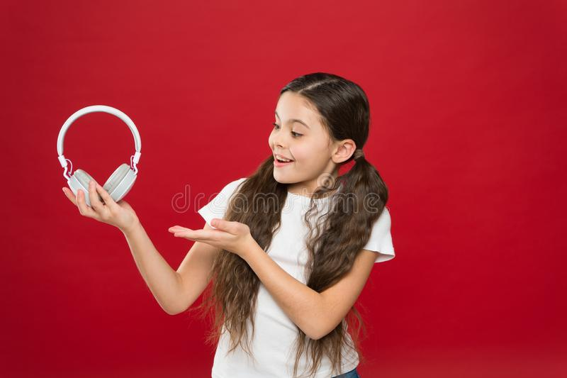 Girl listen music headphones on red background. Modern gadget concept. Music taste. Music plays an important part lives. Teenagers. Powerful effect music stock photography