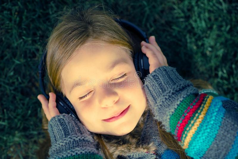 Girl Listen Music. Girl with Wireless Headphones Enjoying Music Laying on Grass in a Park stock photography