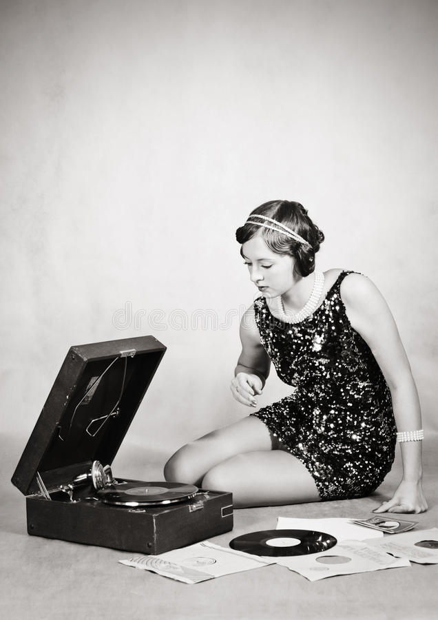 Girl listening to gramophone records. Vintage stock photo