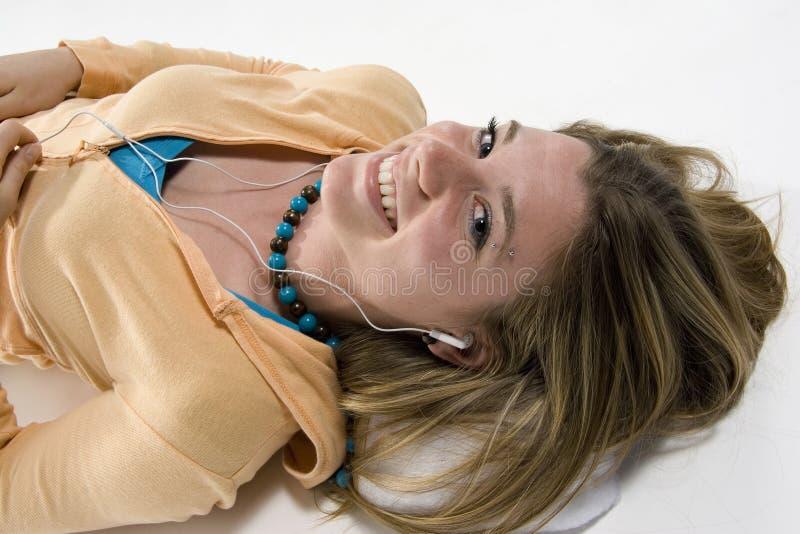 Girl listening to music. Teenage girl lying on floor listening to iPod royalty free stock photography