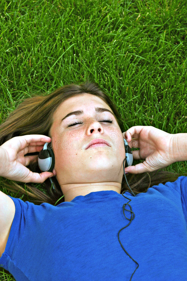 Girl Listening To Music. Laying in the Grass royalty free stock image