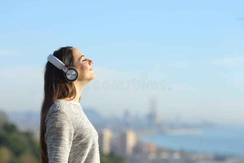 Girl listening to music breathing standing outdoors royalty free stock images