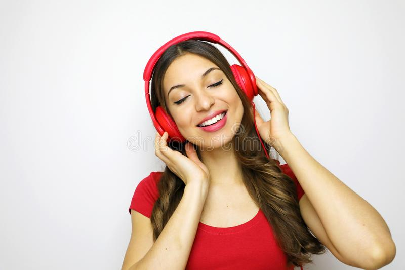 Girl listening to music enyoying her time with closed eyes on white background. Music concept. stock photography