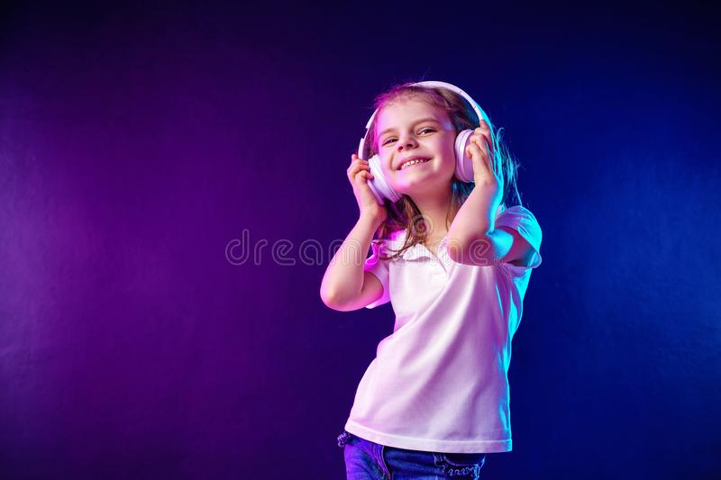 Girl listening to music in headphones on dark colorful background . Dancing girl. Happy small girl dancing to music. Girl of 7 years old listening to music in royalty free stock photography