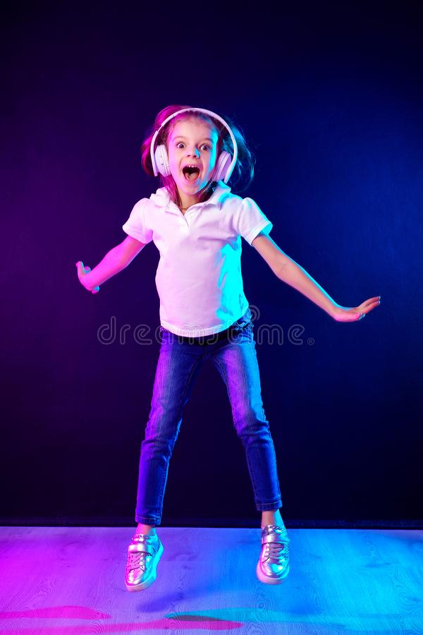Girl listening to music in headphones on dark colorful background . Dancing girl. Happy small girl dancing to music. Girl of 7 years old listening to music in royalty free stock photos