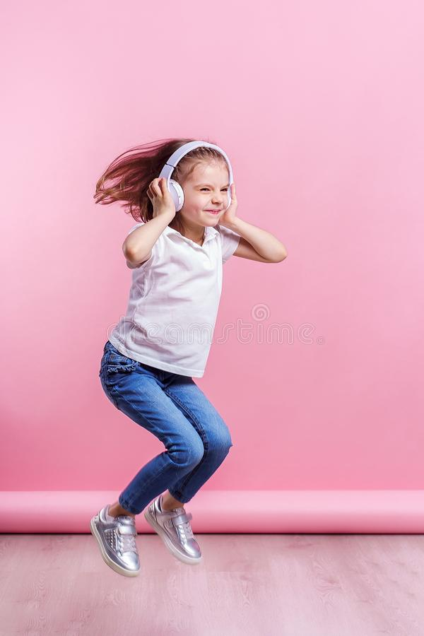 Girl listening to music in headphones on pink background. Dancing girl. Happy small girl dancing to music. Cute child stock images