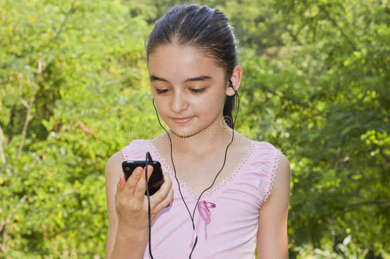 Girl listening to music on a smartphone stock photo