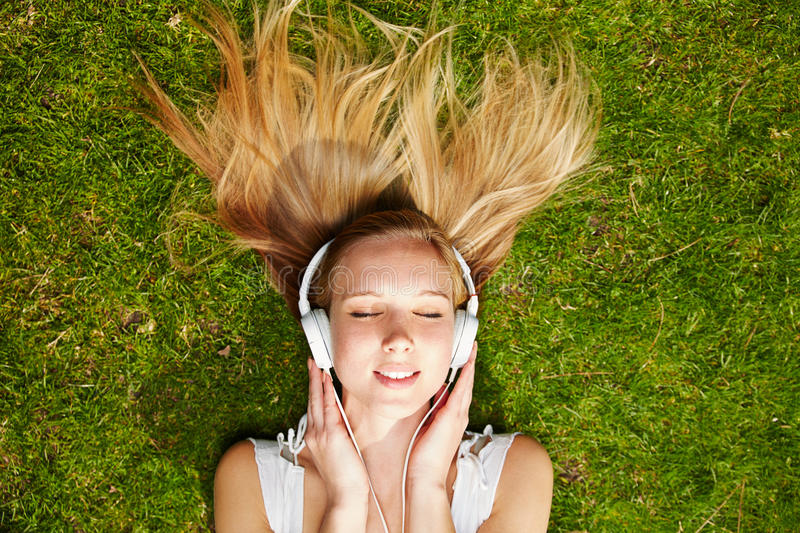 Girl listening to music streaming in summer stock photo
