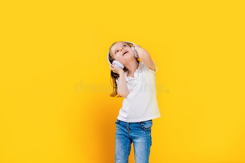 Girl listening to music in wireless headphones on yellow background . Dancing girl. Happy small girl dancing to music. Girl of 7 years old listening to music in stock photography