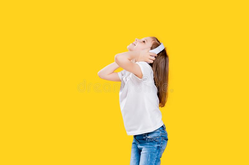 Girl listening to music in wireless headphones on yellow background . Dancing girl. Happy small girl dancing to music. Girl of 7 years old listening to music in royalty free stock image