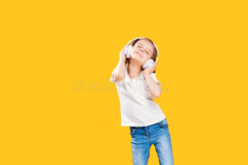 Girl listening to music in wireless headphones on yellow background . Dancing girl. Happy small girl dancing to music. Girl of 7 years old listening to music in royalty free stock photo