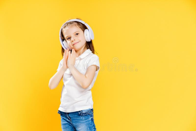 Girl listening to music in wireless headphones on yellow background . Dancing girl. Happy small girl dancing to music. Girl of 7 years old listening to music in stock photo