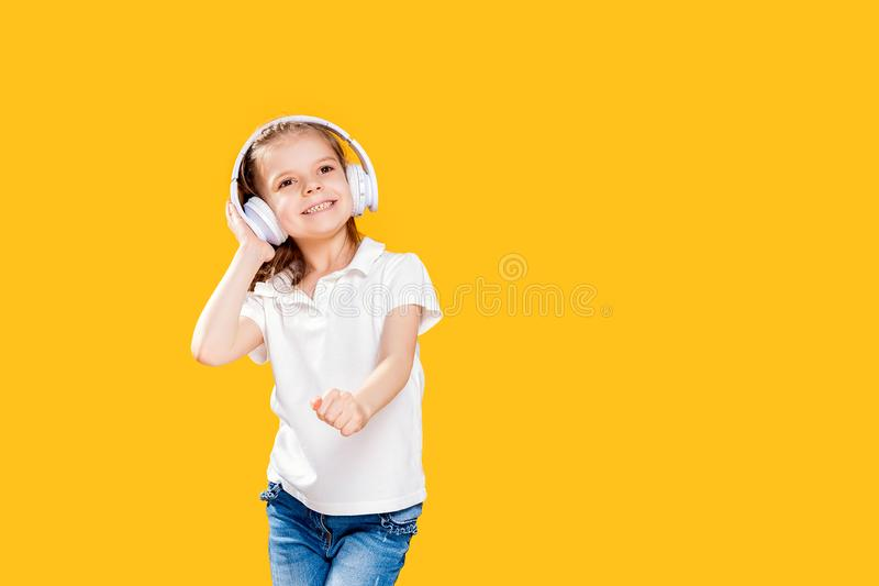 Girl listening to music in wireless headphones on yellow background . Dancing girl. Happy small girl dancing to music. Girl of 7 years old listening to music in stock image