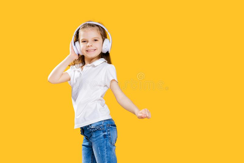 Girl listening to music in wireless headphones on yellow background . Dancing girl. Happy small girl dancing to music. Girl of 7 years old listening to music in royalty free stock images
