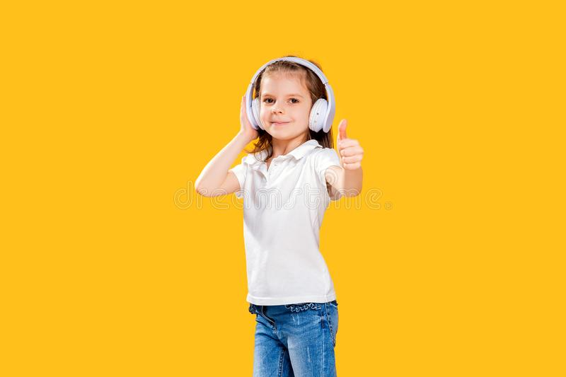 Girl listening to music in wireless headphones on yellow background . Dancing girl. Happy small girl dancing to music. Girl of 7 years old listening to music in royalty free stock photography