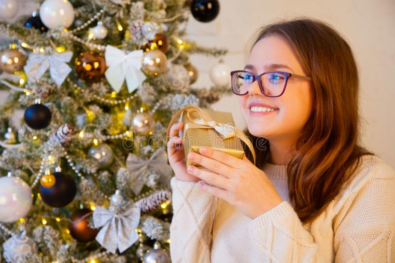 A girl listens to a box with a gift. He tries to guess which gif. The girl sits near the Christmas tree and opens the golden gifts. Christmas fireplace and a lot stock photography