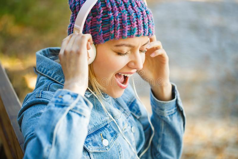 Girl listens to music in headphones. Smiling girl relaxing, music a smartphone and headphones. Outdoors portrait of a royalty free stock image