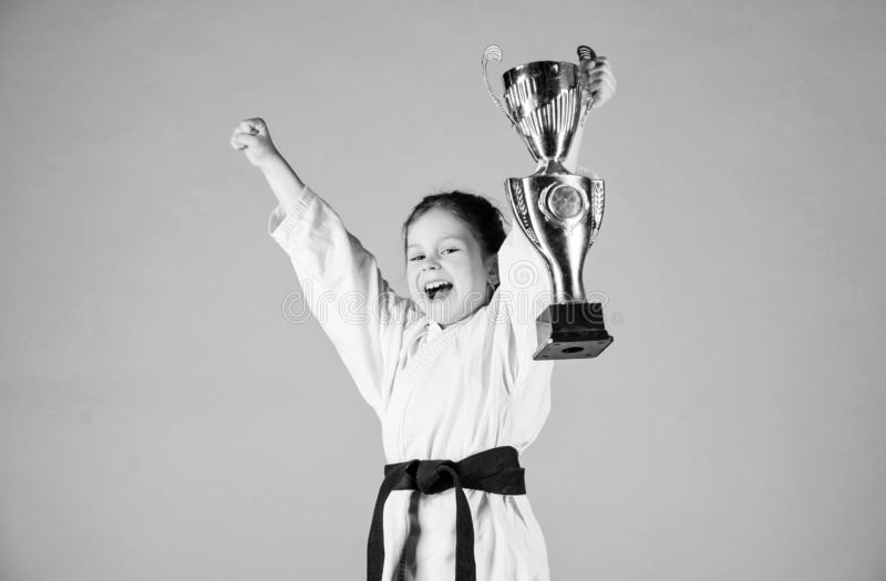 Girl little child in white kimono with belt. Karate fighter child. Karate sport concept. Self defence skills. Karate. Gives feeling of confidence. Strong and stock image