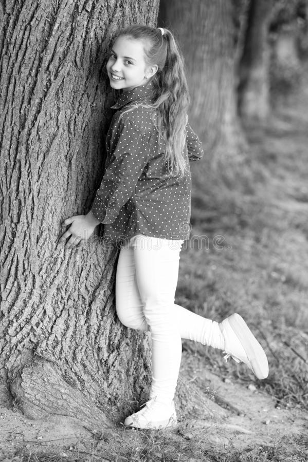 Girl little cute child enjoy peace and tranquility at tree trunk. Calm and peaceful. Life balance. Peaceful mood. Good stock image