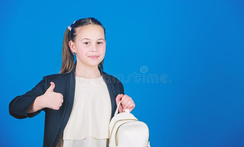 Girl little fashionable cutie carry backpack. Kids fashion trend concept. Schoolgirl formal style clothes with small. Cute backpack. Do not forget your backpack royalty free stock photos