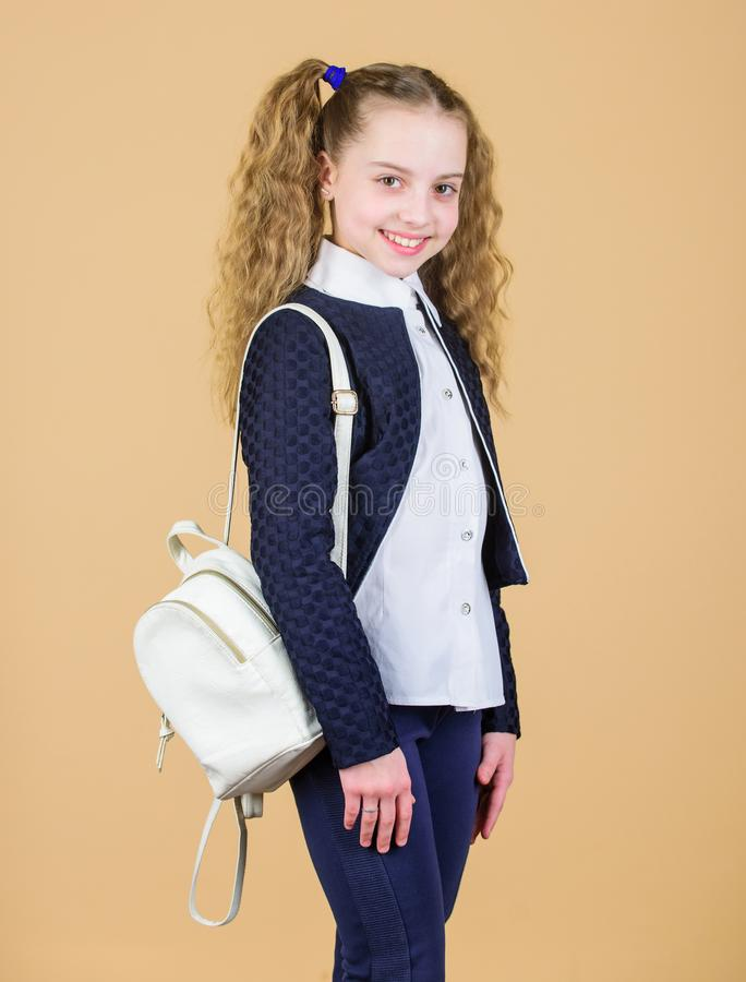 Girl little fashionable cutie carry backpack. Popular useful fashion accessory. Schoolgirl with small leather backpack. Carry bag comfortable. Stylish mini stock photo