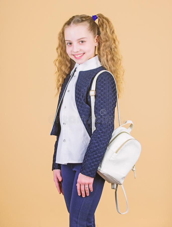 Girl little fashionable cutie carry backpack. Popular useful fashion accessory. Schoolgirl with small leather backpack. Carry bag comfortable. Stylish mini royalty free stock images