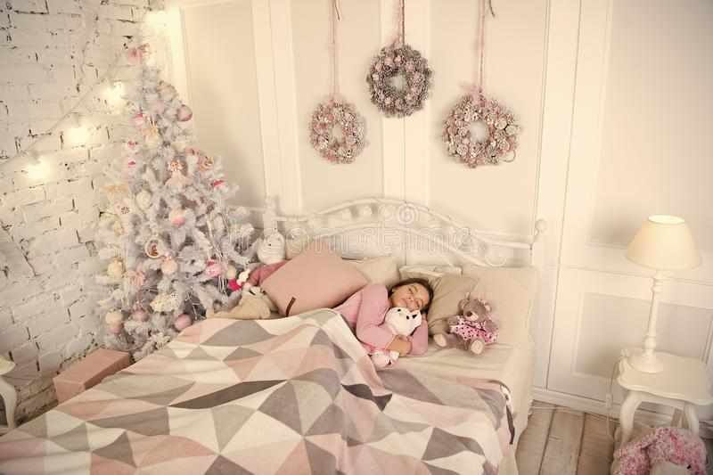 Girl little kid relaxing on bed light interior with christmas decorations. Christmas eve concept. Child waiting royalty free stock image