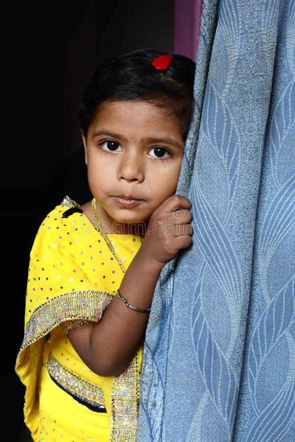 The Girl. A little girl with yellow dress -posed in the home. in India stock photos