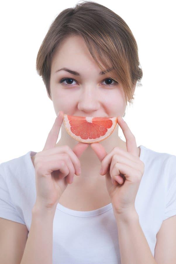 Girl with lobule of grapefruit. Portrait of girl with lobule of grapefruit isolated on white stock image