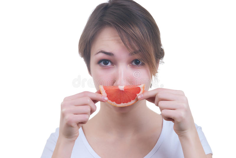 Girl with lobule of grapefruit. Portrait of girl with lobule of grapefruit isolated on white royalty free stock photos