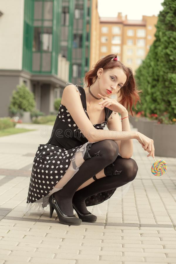Girl with lollipop. Attractive young woman with lollipop in black dress and black stockings sitting on street royalty free stock photo