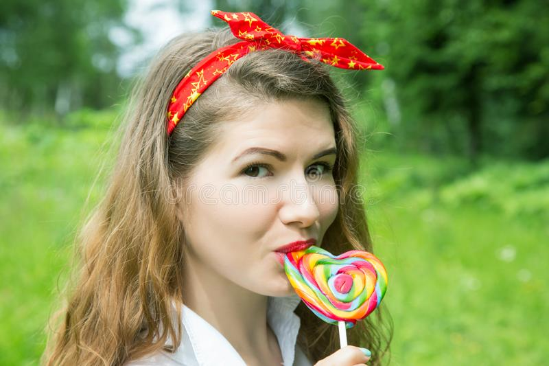 Girl with a lollipop in the trees in the summer. Day royalty free stock photography