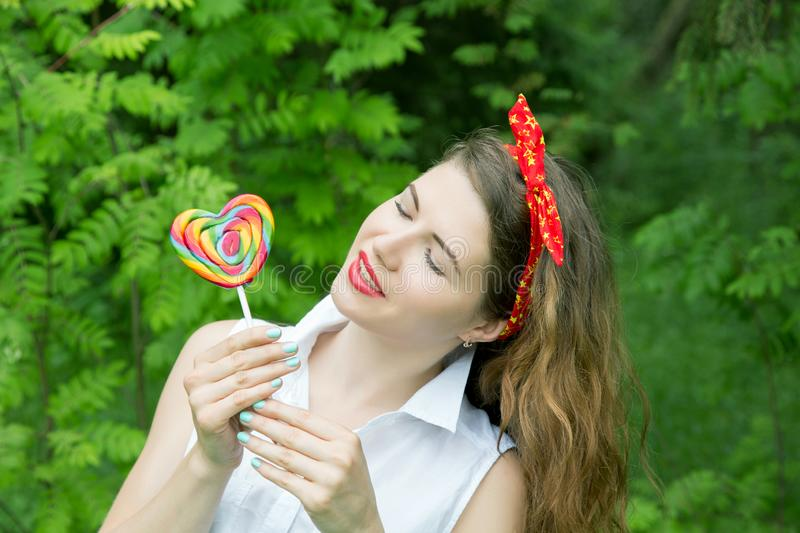 Girl with a lollipop in the trees in the summer. Day royalty free stock image