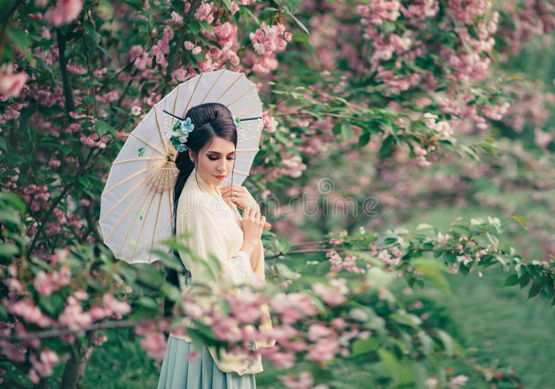 A girl with long, black hair decorated with Kandzashi, flowers and long pins with crystal beads. Geisha in a bamboo royalty free stock photos