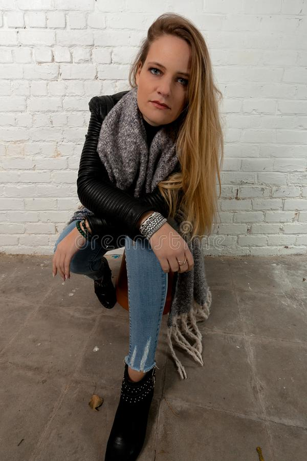 Blond girl sitting green eyes white brick wall. Girl with long blond hair and green eyes in leather jacket and knitted grey scarf for the winter sitting casually royalty free stock photos